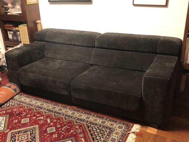 Sofá preto em tecido com encosto de cabeça e assentos